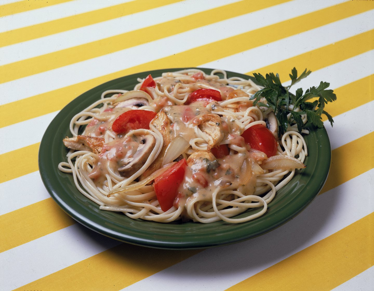 A dish of Italian-style pasta noodles with a chicken, onion, mushroom, and tomato sauce, and parsley, sits on a yellow and white striped surface, 1970s. (Photo by Hulton Archive/Getty Images)