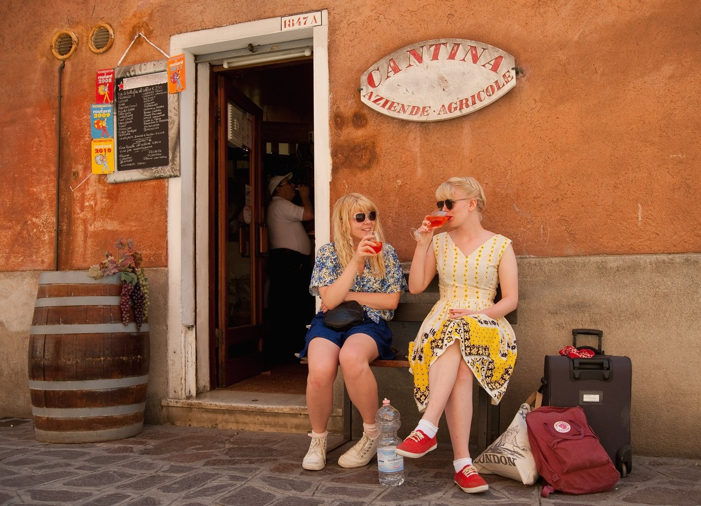 VENICE, ITALY - JUNE 17:  Two tourists enjoy a Spritz (a powerful mixture of white wine, Campari and soda water) in front of a traditiona bacaro on June 17, 2011 in Venice, Italy. The bacari are the local down to earth version of wine bars which serve 'ciccheti, a kind of Tapas traditionally washed down with a glass of wine, and Venetians stop to snack and socialize before and after meals. (Photo by Marco Secchi/Getty Images)