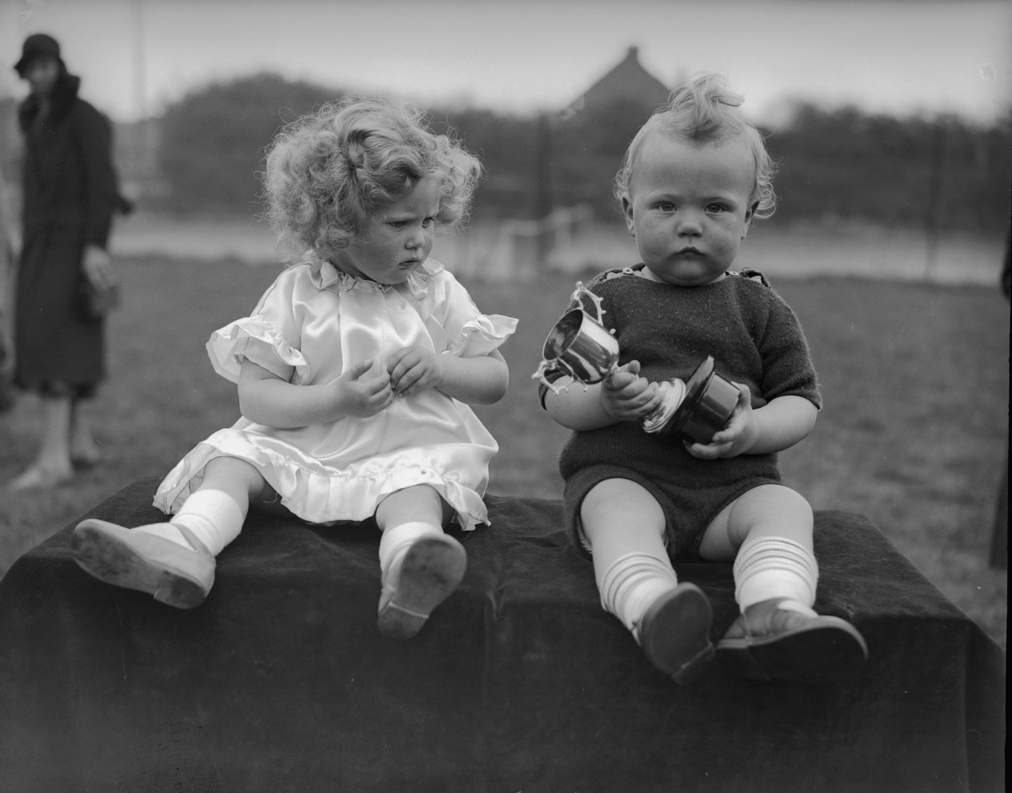 8th May 1934:  Twins Michael and Mary Kerby fail to convey any enthusiasm upon winning a trophy in a Baby Show at Ruislip, Middlesex.  (Photo by Martin/Fox Photos/Getty Images)