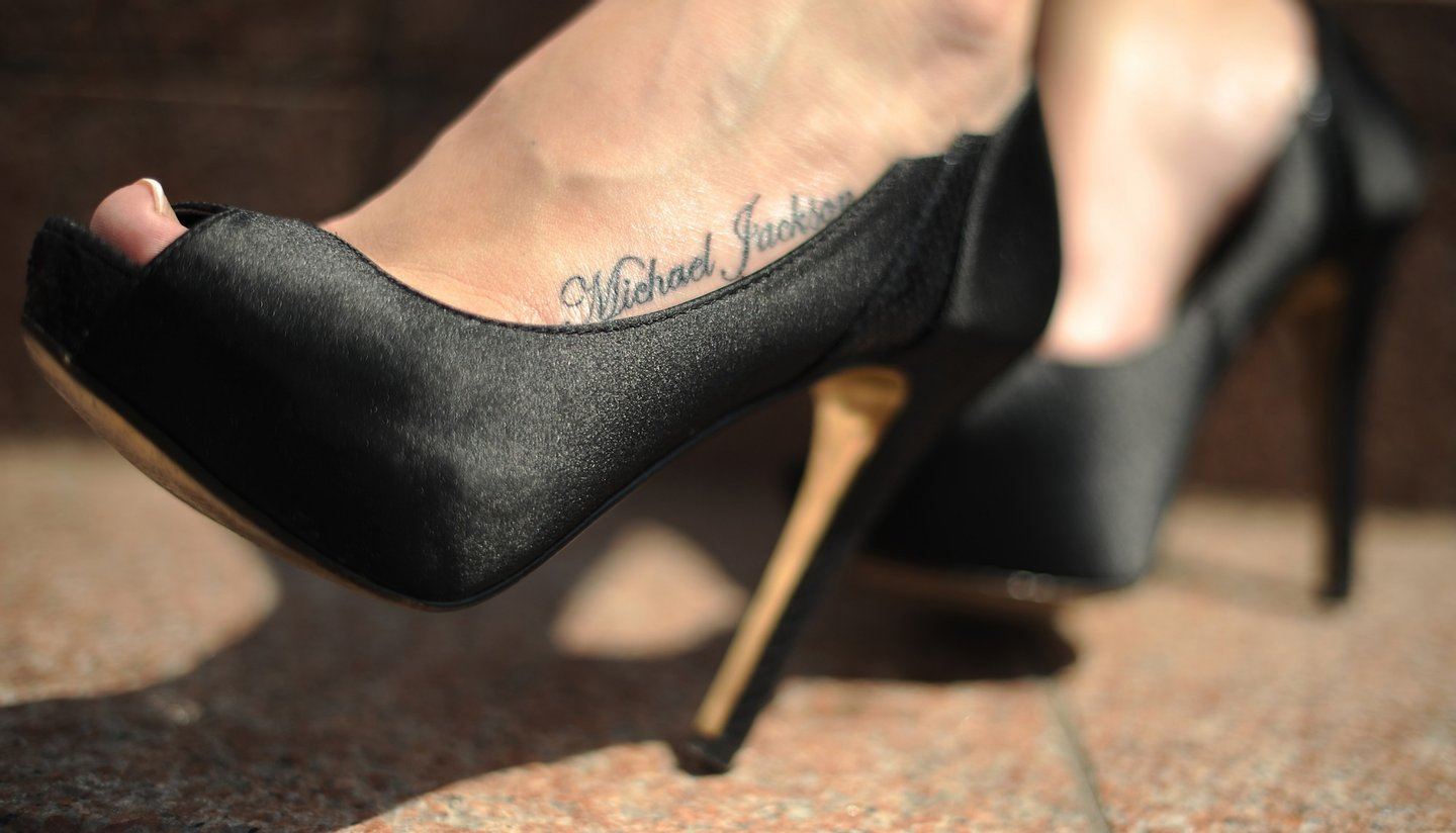 "A woman displays a tattoo of Michael Jackson's name on her foot outside the 02 arena in London, on June 25, 2010, as fans gather to remember the king of pop's death one year ago. Michael Jackson fans around the world began Friday marking the first anniversary of the music icon's death, with events from candlelight vigils to slumber parties planned in honor of the tragic superstar. Jackson, 50, died from a drug overdose at a rented Los Angeles mansion on June 25 last year, a seismic celebrity death that triggered a global outpouring of tributes for the eccentric genius known as ""The King of Pop."" AFP PHOTO/BEN STANSALL (Photo credit should read BEN STANSALL/AFP/Getty Images)"