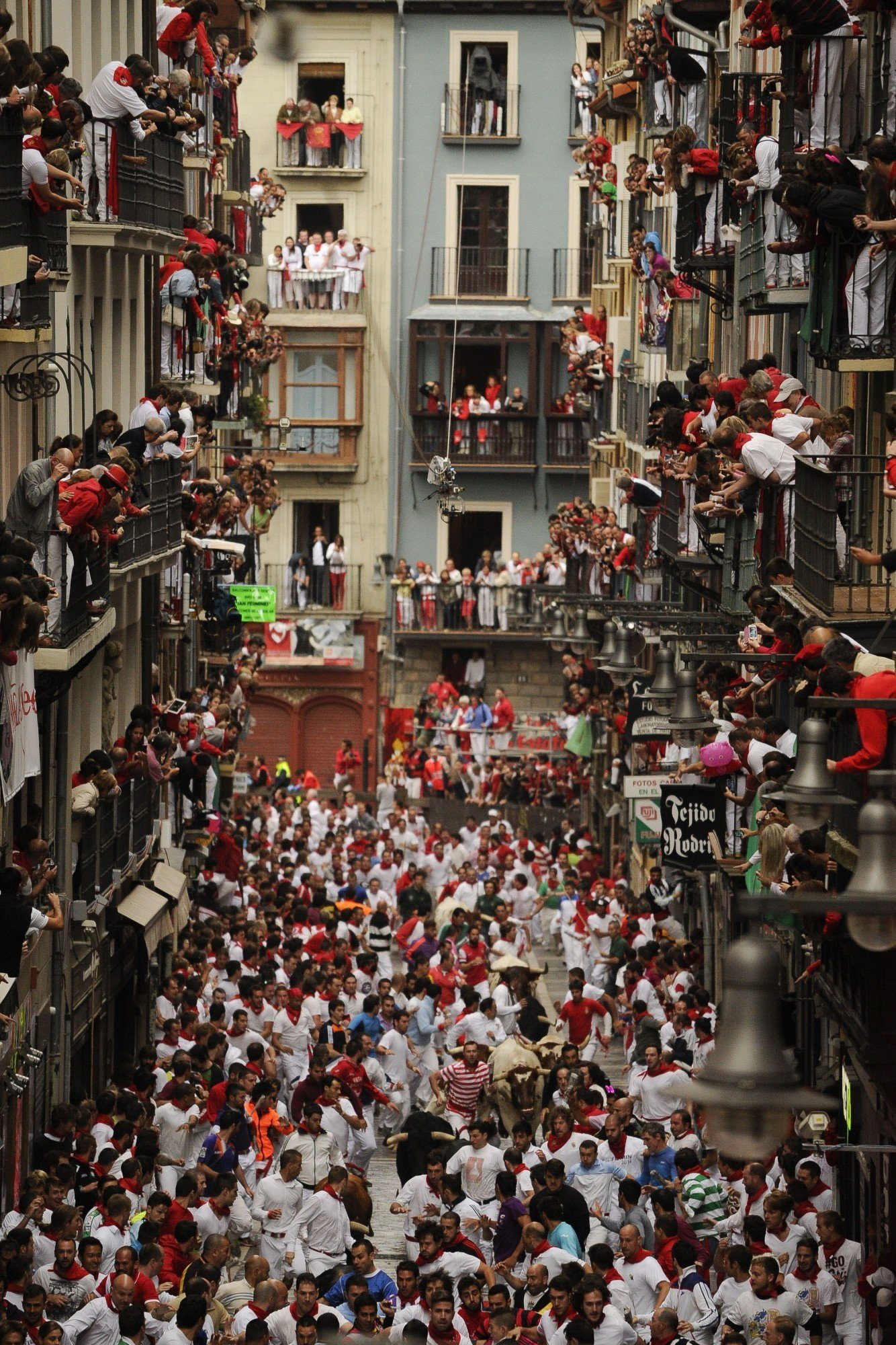 People standing on balconies look at participants as they run in front of Victoriano del Rio Cortes' bulls during the third bull-run of the San Fermin Festival in Pamplona, northern Spain, on July 9, 2014. The festival is a symbol of Spanish culture that attracts thousands of tourists to watch the bull runs despite heavy condemnation from animal rights groups.  AFP PHOTO / PEDRO ARMESTRE        (Photo credit should read PEDRO ARMESTRE/AFP/Getty Images)