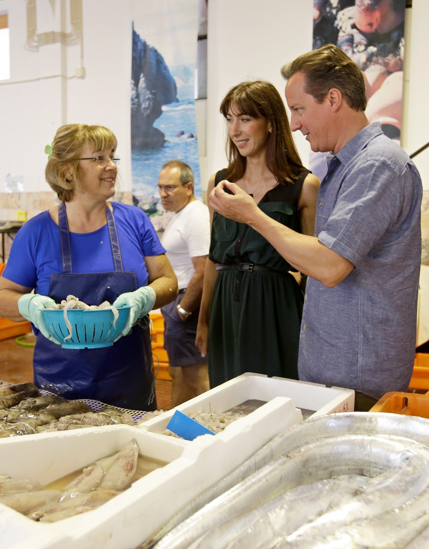 British Prime Minister David Cameron and his wife Samantha buy squid in a market while on holiday in Aljezur, in the southwestern coast of Portugal, on July 26, 2013. AFP PHOTO/POOL/ARMANDO FRANCA        (Photo credit should read ARMANDO FRANCA/AFP/Getty Images)