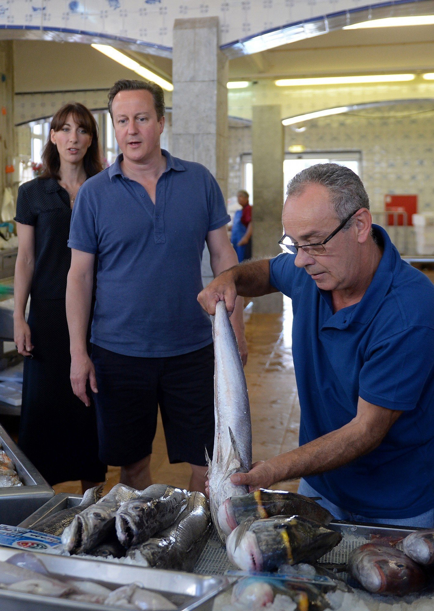 Britain's Prime Minister David Cameron (2nd L) and his wife Samantha (L) are pictured as they visit a seafood market while on holiday in Cascais in Portugal, on August 5, 2014. A British minister, Baroness Sayeeda Warsi, who was the first Muslim woman to sit in the Cabinet has resigned over the British government's policy on Gaza, she said Tuesday.  AFP PHOTO / FRANCISCO LEONG/POOL