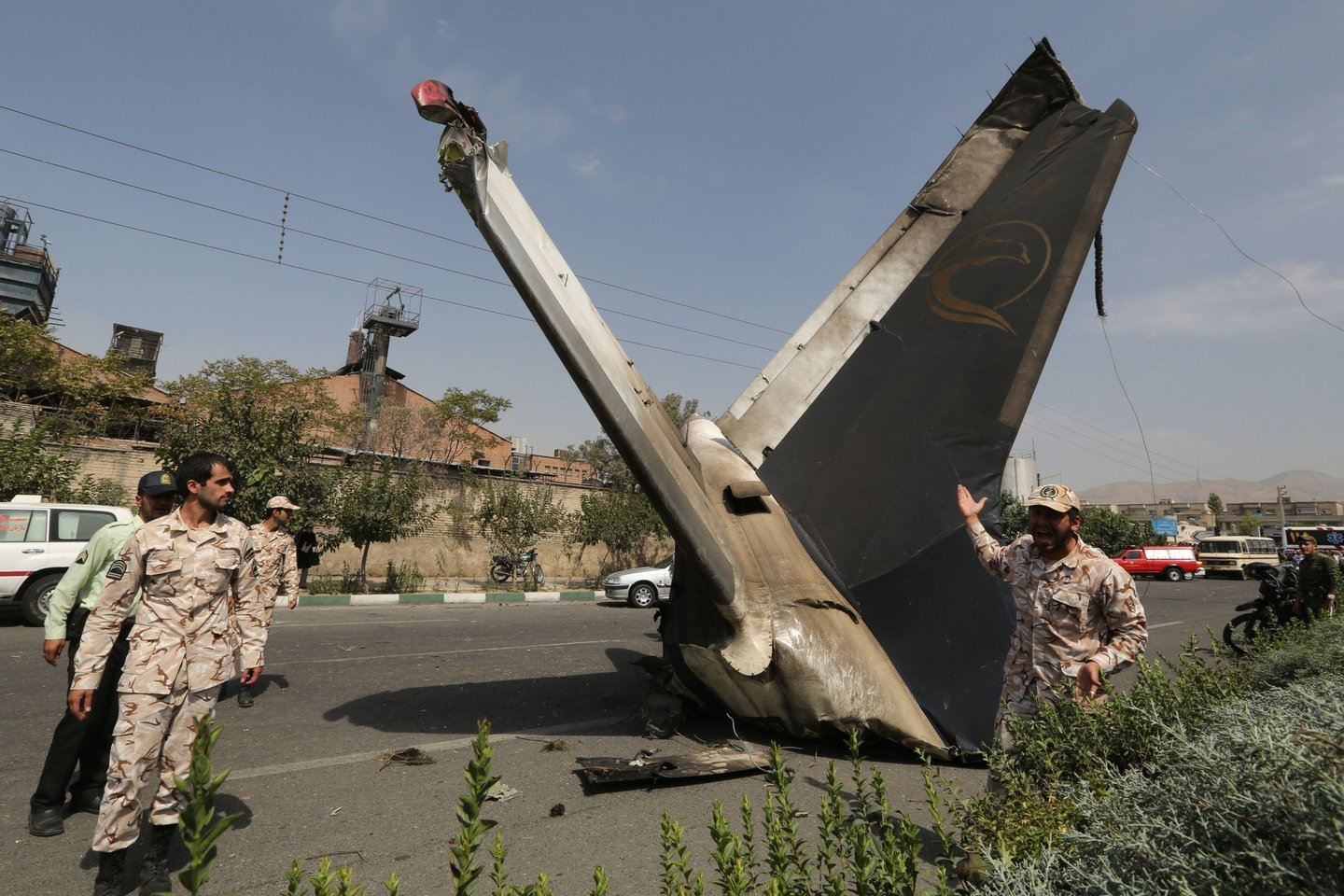 A member of the Iranian Revolutionary Guards reacts as he stands next to the remains of a plane that crashed near Tehran's Mehrabad airport on August 10, 2014. A civilian airliner crashed on take-off near the Mehrabad airport in the capital, Iranian news agencies said, with reports that almost 50 people were killed. AFP PHOTO / ATTA KENARE        (Photo credit should read ATTA KENARE/AFP/Getty Images)