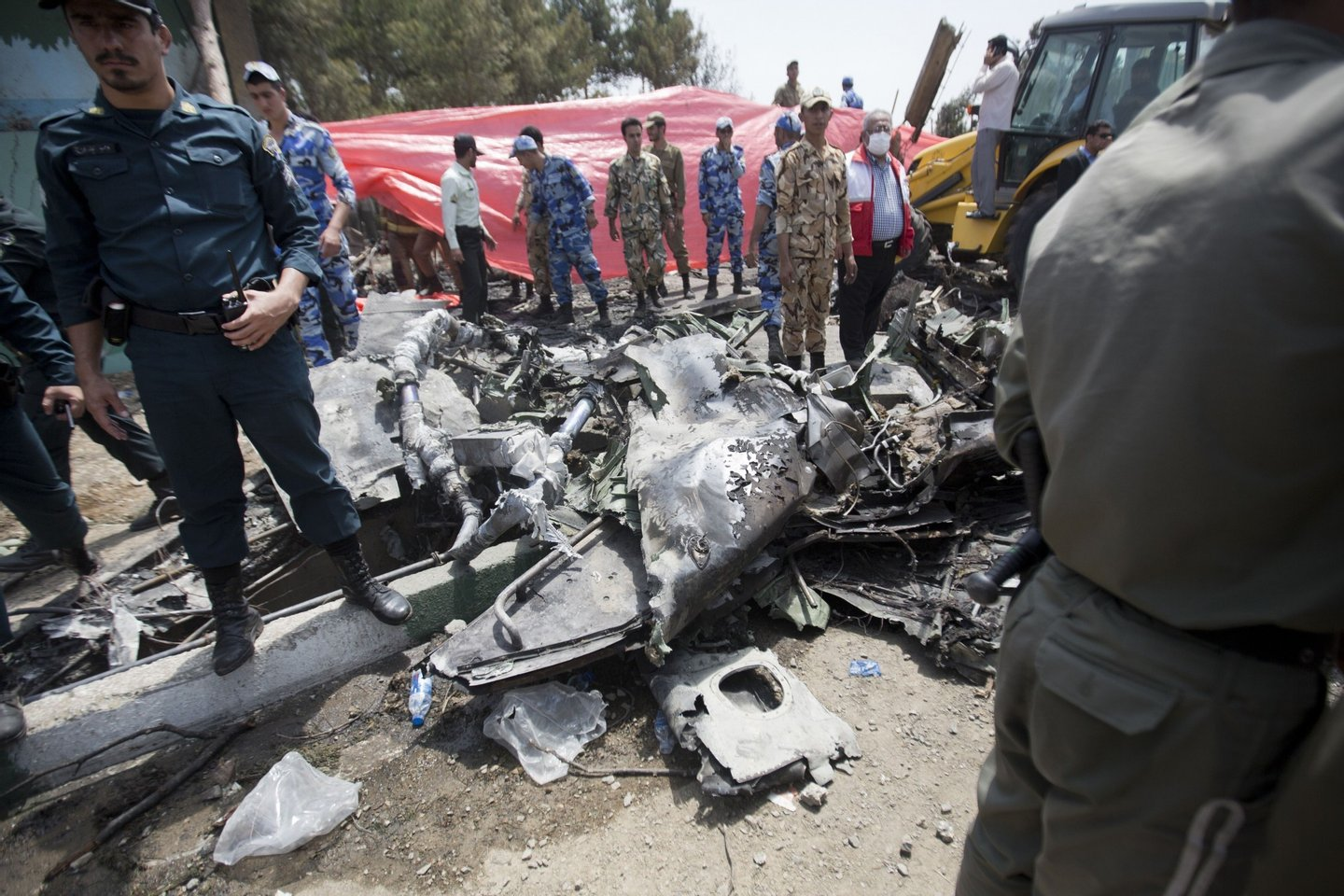 Iranian security forces secure the scene of a plane crash near Tehran's Mehrabad airport on August 10, 2014. An Iranian passenger plane crashed moments after takeoff from Tehran, killing at least 38 people on board and narrowly avoiding many more deaths when it plummeted to earth near a busy market. AFP PHOTO/BEHROUZ MEHRI        (Photo credit should read BEHROUZ MEHRI/AFP/Getty Images)