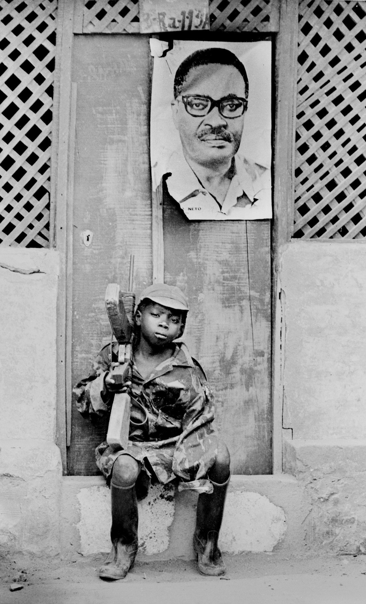 HUAMBO, ANGOLA:  A young soldier of the Popular Movement for the Liberation of Angola (MPLA) is seated on a doorstep 23 February 1976 in Huambo. Over his heads hangs the portrait of his leader Agostinho Neto. Former Portuguese colony, the Republic of Angola went to a civil war after its independence in1975, with three infernal factions, the Marxists MPLA, UNITA (The National Union for the Total Independence of Angola) and the FLNA (National Front for the Liberation of Angola).  Un jeune soldat du Mouvement Populaire de LibTration de l'Angola (MPLA) est assis sur le pas d'une porte le 23 fTvrier 1976 a Huambo. Au dessus de lui, est accrochT un portrait de son leader Agostinho Neto. Ancienne colonie portugaise, la RTpublique d'Angola connait aprFs son indTpendance en 1975 une guerre civile opposant trois factions, les marxistes MPLA, l'UNITA (Union National pour l'IndTpendance Totale de l'Angola) et le FLNA (Front National de LibTration de l'Angola). (Photo credit should read AFP/Getty Images)