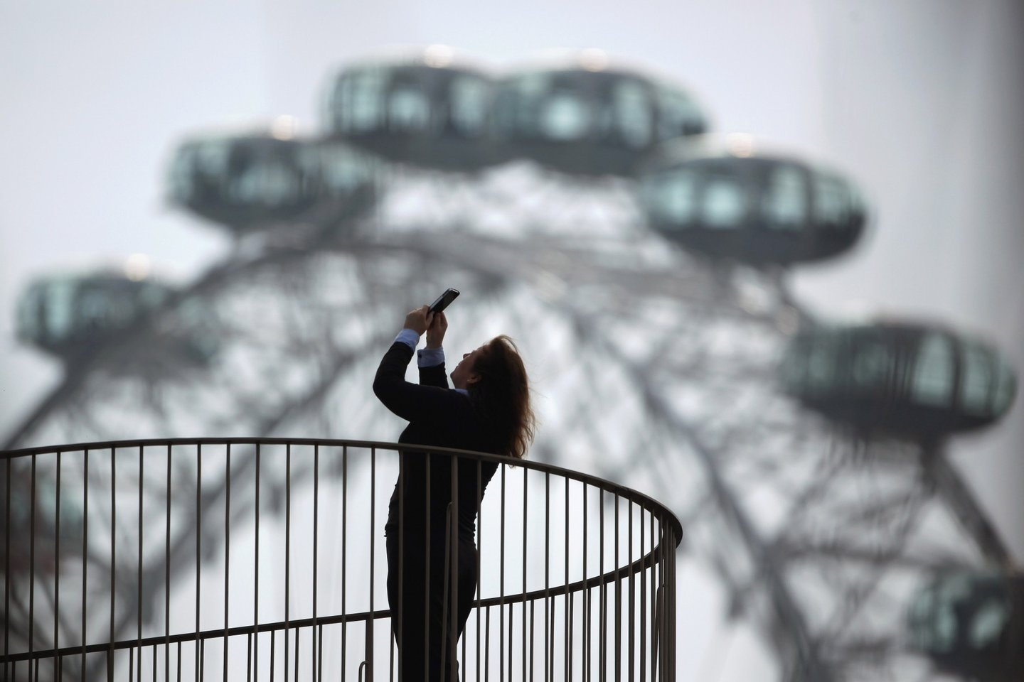 LONDON, ENGLAND - MARCH 22: A woman takes a photograph from a balcony near the London Eye on March 22, 2012 in London, England. A full rotation of the giant Ferris wheel, the largest of it's kind in Europe, takes 30 minutes and rises to a height of 135 metres. On a clear day one can see for 40km from the top. (Photo by Dan Kitwood/Getty Images)