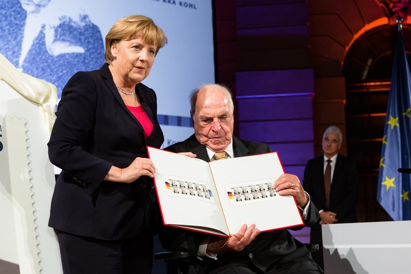 BERLIN, GERMANY - SEPTEMBER 27:  German Chancellor Angela Merkel (L) presents a commemorative postal stamp showing former German Chancellor Helmut Kohl as the former Chancellor (R) looks on at a gala evening in Kohl's honour at the Deutsches Museum on September 27, 2012 in Berlin, Germany. Guests from politics, church and society attended the event to honour Kohl on the 30th anniversary of Kohl becoming chancellor. During his chancellorship Kohl facillitated the end of the Cold War, the fall of the Berlin Wall and German reunification.  (Photo by Christian Marquardt - Pool / Getty Images)