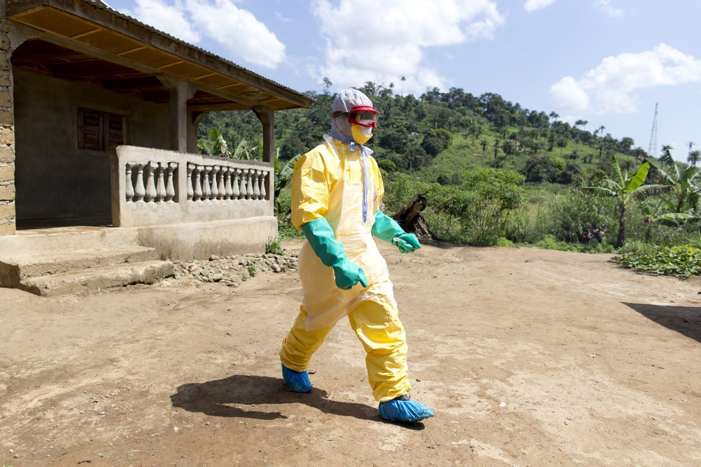 An health worker from Guinea's Red Cross wearing a Personal Protective Equipments (PPE) leaves the house of a victim of the Ebola virus in Patrice disitrict in Macenta, in Guinea on November 21, 2014.  The deadliest Ebola epidemic on record has killed more than 5,000 people in west Africa and infected almost three times that number, according to the World Health Organization. The virus emerged in Guinea at the start of the year and has infected around 1,900 Guineans, killing almost 1,200. AFP PHOTO KENZO TRIBOUILLARD        (Photo credit should read KENZO TRIBOUILLARD/AFP/Getty Images)