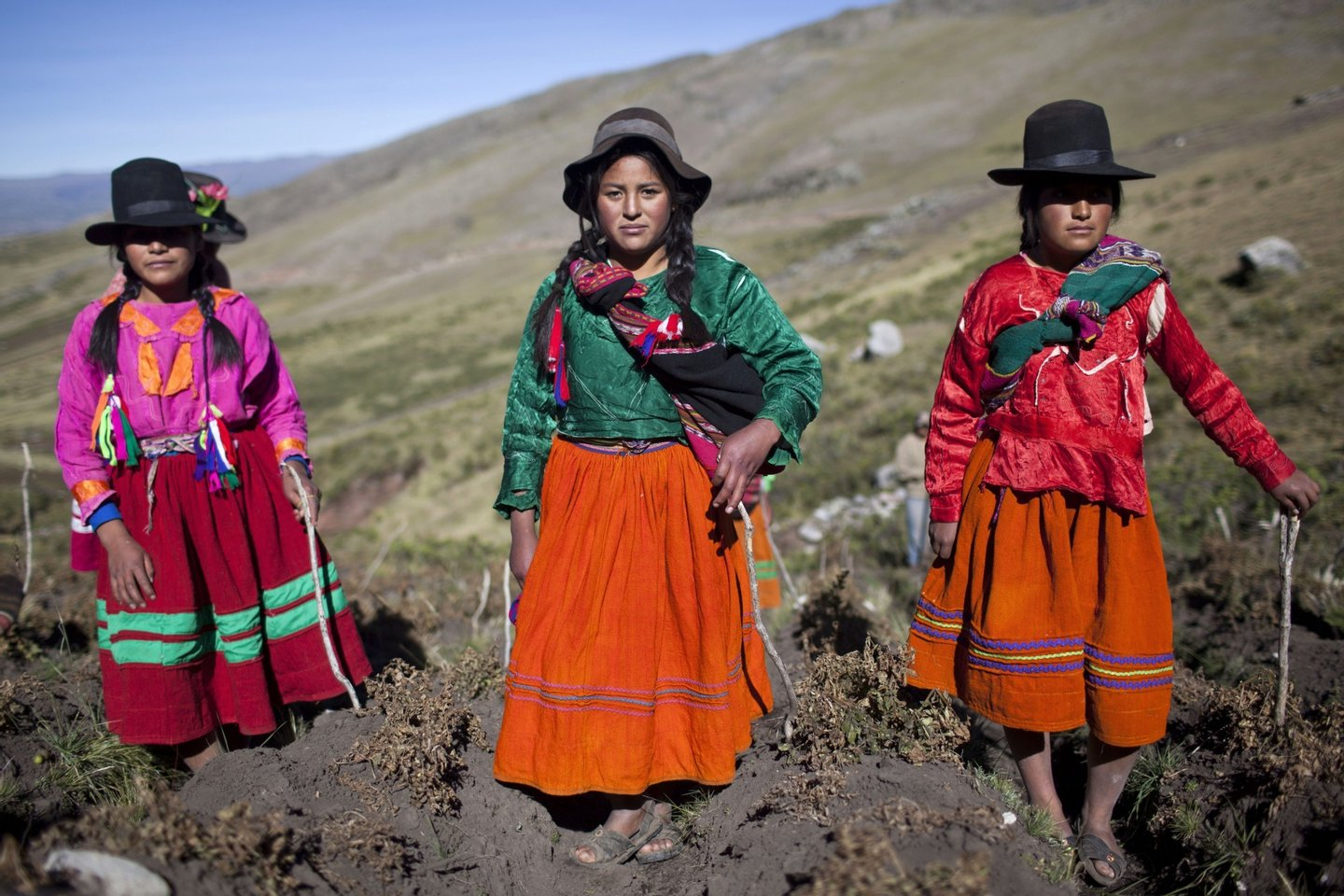 Andean girls pose for a picture during the harvest of native potatoes in the Pomacochas district of  the department of Apurimac, 900 kms southeast from Lima on May 26, 2014. Peru is the country with the greatest diversity of potatoes in the world, with some 3,800 types, differing in size, shape, color, skin, pulp, texture and  taste,  all of which have their place in Peruvian cuisine.   AFP PHOTO/ERNESTO BENAVIDES        (Photo credit should read ERNESTO BENAVIDES/AFP/Getty Images)