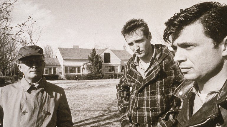American novelist, short story writer, and playwright Truman Capote (1924 - 1984) (left), dressed in an overcoat, glasses, and hat, stands on a lawn near American actors Scott Wilson and Robert Blake (right), both dressed in character, while on location filming the film adaptation of Capote's book 'In Cold Blood,' Kansas, 1967. (Photo by Hulton Archive/Getty Images)