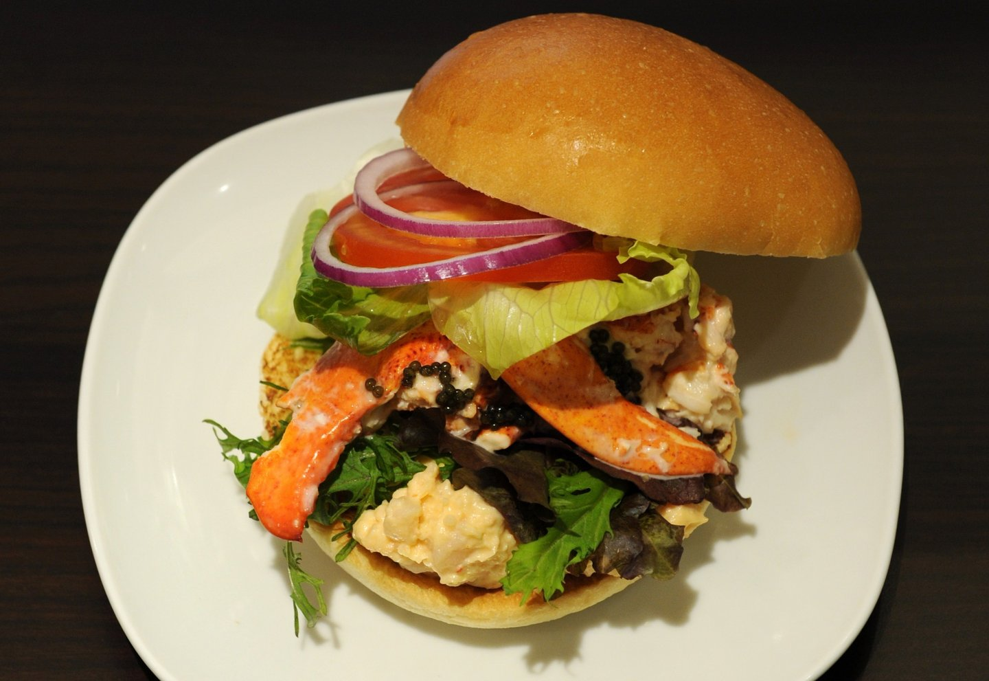 This picture shows the Lobster and Caviar burger featuring Canadian lobster and contains whole lobster pieces as well as a lobster salad made with a mustard mayonnaise as well as a sprinkle of caviar produced by Wendy's Japan as part of the campany's opening of their second restaurant in Roppongi, Tokyo on August 17, 2012. Wendy's Japan introduced two new burgers to their Japan Premium line of burgers which features fancy ingredients.      AFP PHOTO / KAZUHIRO NOGI        (Photo credit should read KAZUHIRO NOGI/AFP/GettyImages)
