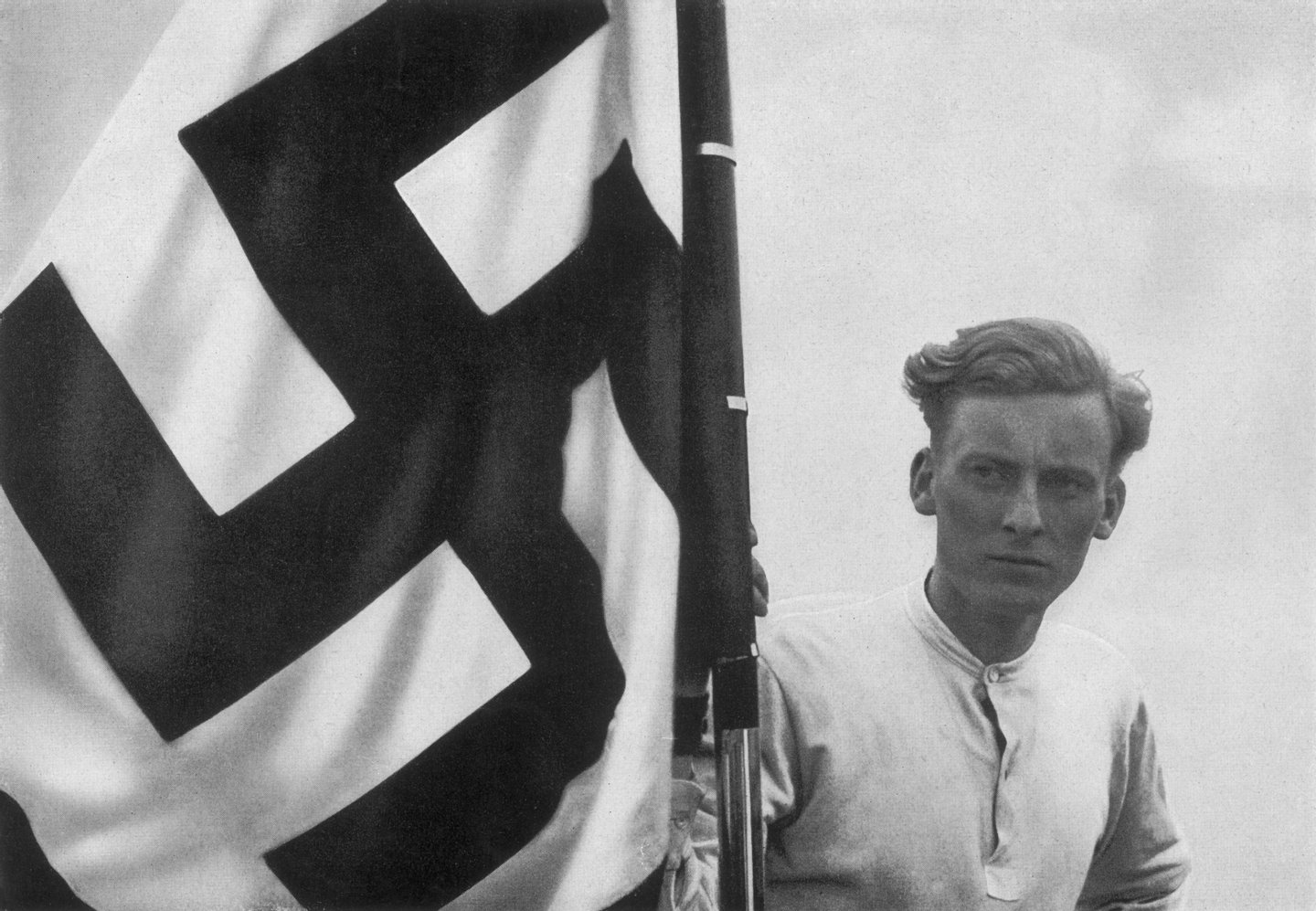 circa 1935:  A member of the Hitler Youth with a swastika flag at a Nazi rally in Germany.  Original Publication: From a series of collectable images published in Germany during the Nazi period, entitled 'Deutschland Erwacht' (Germany Awakes).  (Photo by Hulton Archive/Getty Images)