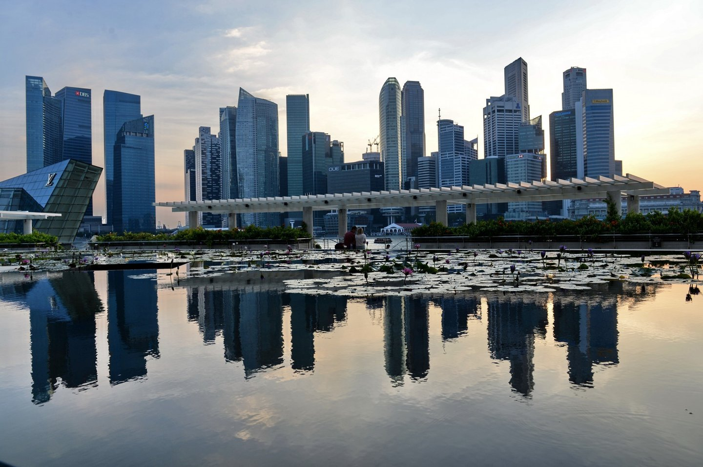A general view of the financial district skyline is reflected in a pond in Singapore on March 6, 2014 in Singapore. Singapore played down a global survey showing that it is now the world's most expensive city, a finding which has triggered outrage among Singaporeans struggling with rising costs. AFP PHOTO / ROSLAN RAHMAN        (Photo credit should read ROSLAN RAHMAN/AFP/Getty Images)