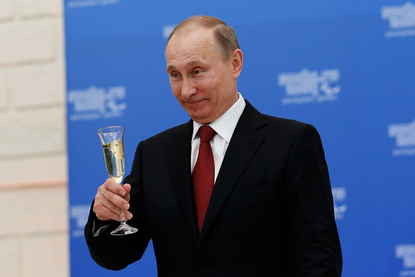 SOCHI, RUSSIA - MARCH 13: Russian President Vladimir Putin holds a glass of champagne during a lunch hosted by the office of the Russian President Vladimir Putin for the Presidents of the International Paralympic Committee member organisations during the 2014 Sochi Paralympic Games on March 13, 2014 in Sochi, Russia.  (Photo by Harry Engels/Getty Images)