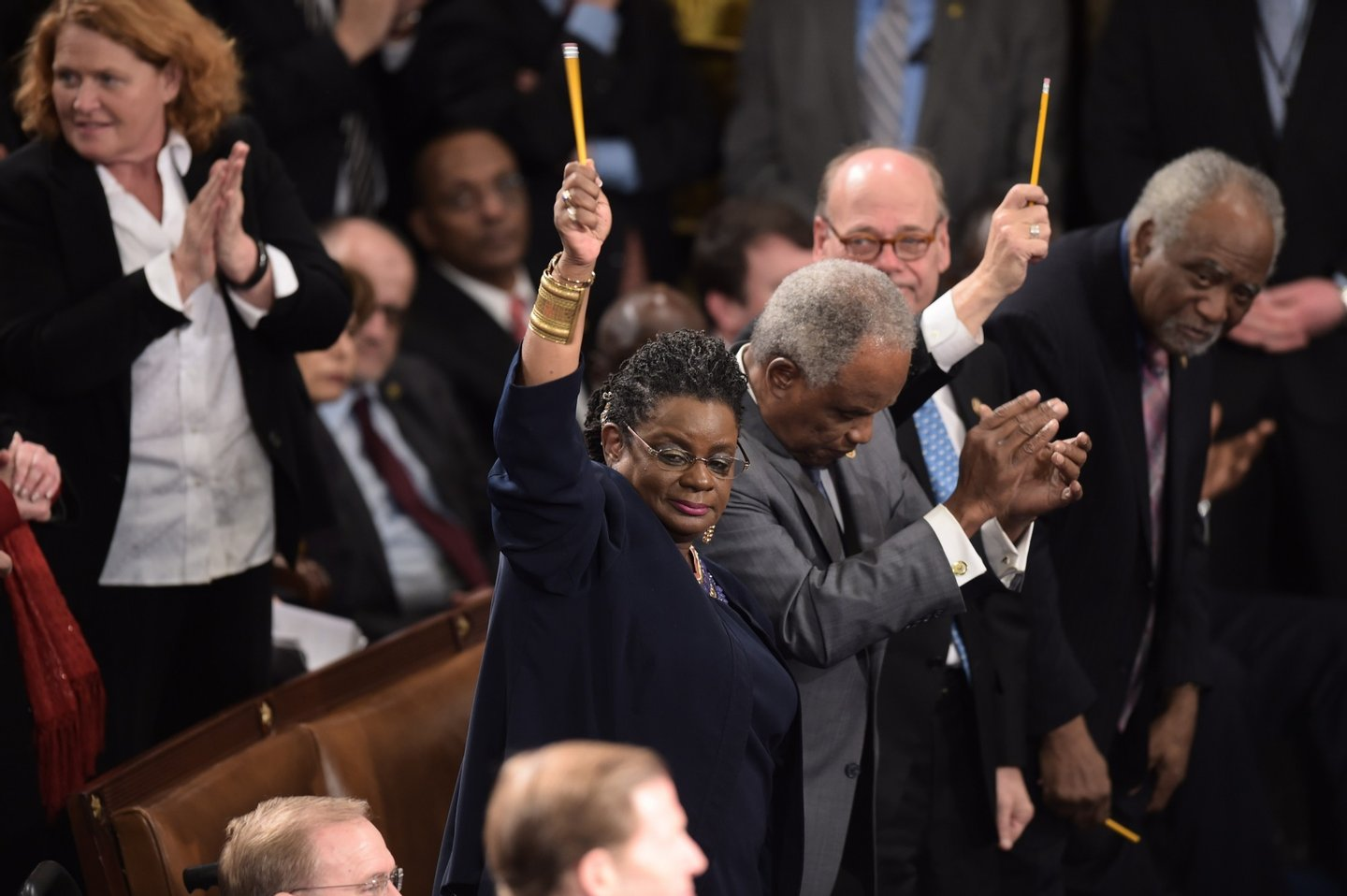 US lawmakers pay tribute to the victims of the Paris attacks by holding up pencils during the State of the Union address by US President Barack Obama, before a joint session of Congress on January 20, 2015 at the US Capitol in Washington, DC.   AFP PHOTO/JIM WATSON        (Photo credit should read JIM WATSON/AFP/Getty Images)