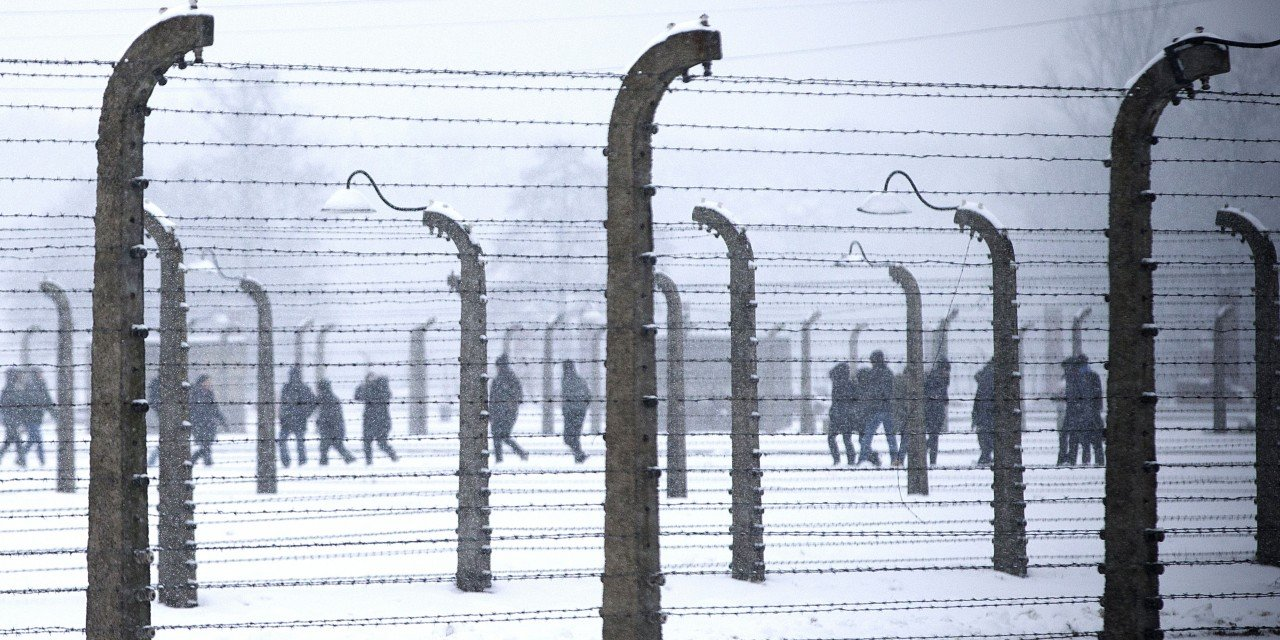 Visitor are seen walking behind barbed-wire fences at the memorial site of the former Nazi concentration camp Auschwitz-Birkenau in Oswiecim, Poland on January 25, 2015, days before the 70th anniversary of the liberation of the camp by Russian forces. AFP PHOTO / JOEL SAGET (Photo credit should read JOEL SAGET/AFP/Getty Images)