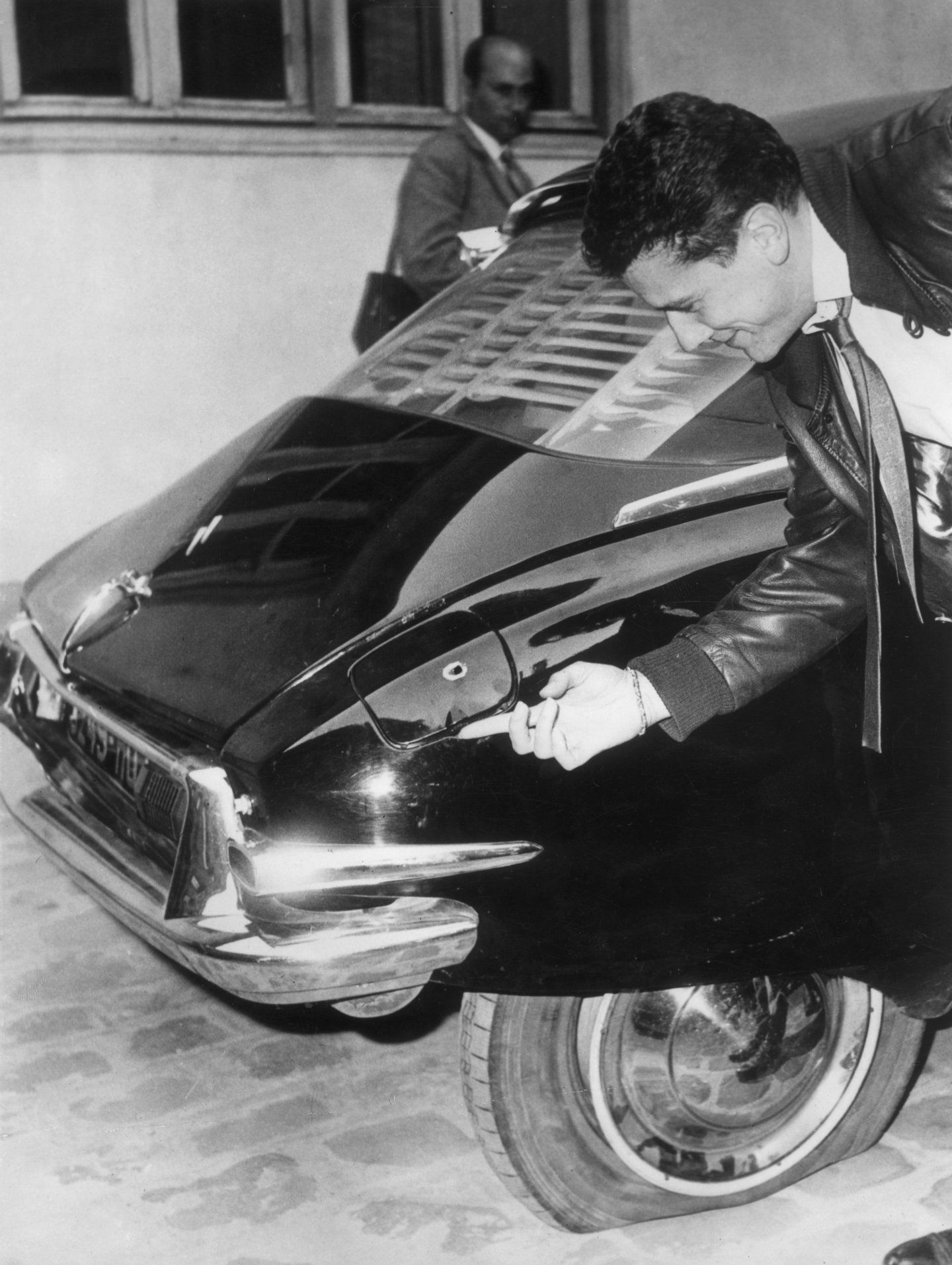 23rd August 1962: A man examines one of the bullet holes in French president General de Gaulle's Citroen DS in Paris, after an assassination attempt in the Paris suburb of Le Petit-Clamart, on 22nd August 1962. (Photo by Keystone/Getty Images)