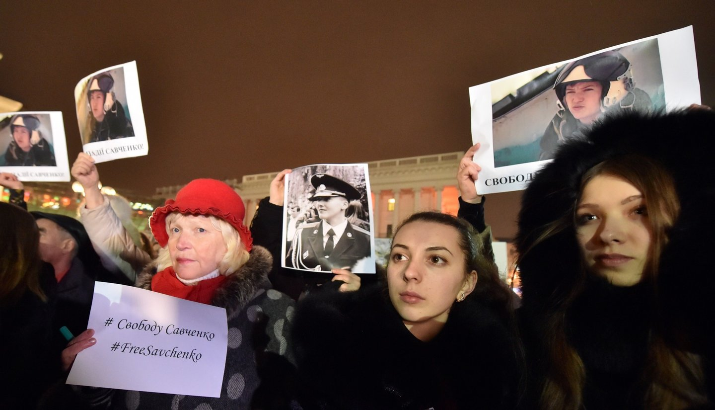 """People hold pictures of first lieutenant of Ukrainian airforce, helicopter pilot Nadiya Savchenko  and placards reading """"Free Savchenko"""" during a rally in Independence Square in Kiev, on January 26, 2015 demanding her liberation by Russia. Savchenko was fighting in a Ukrainian volunteer battalion in east of the country when she was captured by pro-Russian insurgents in eastern Ukraine and later handed over to Russia, where she is being charged with complicity in the deaths of two Russian journalists during the 2014 insurgency in Donbass. AFP PHOTO/ SERGEI SUPINSKY        (Photo credit should read SERGEI SUPINSKY/AFP/Getty Images)"""
