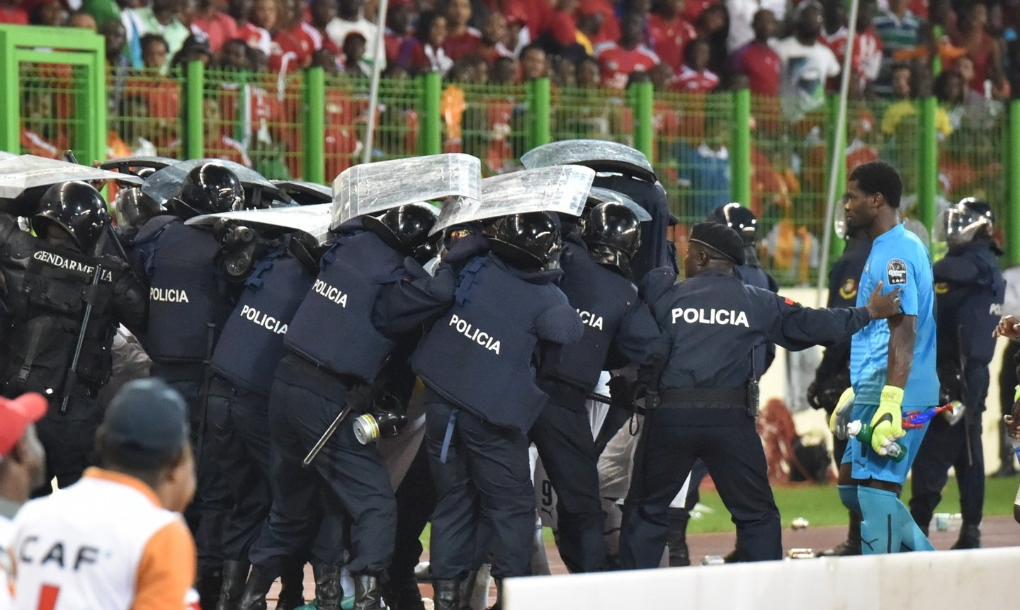 Ghana's national football team players leave the pitch protected by riot police at the half-time of the 2015 African Cup of Nations semi-final football match between Equatorial Guinea and Ghana in Malabo, on February 5, 2015. AFP PHOTO / ISSOUF SANOGO        (Photo credit should read ISSOUF SANOGO/AFP/Getty Images)