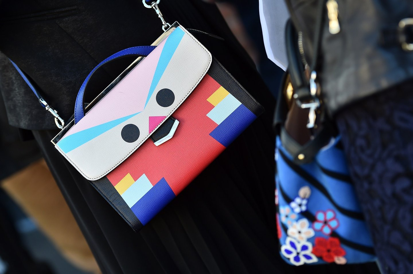 A woman poses with a Fendi bag in the street before the show for fashion house Fendi at the women Fall / Winter 2015/16 Milan's Fashion Week on February 26, 2015.   AFP PHOTO / GABRIEL BOUYS        (Photo credit should read GABRIEL BOUYS/AFP/Getty Images)