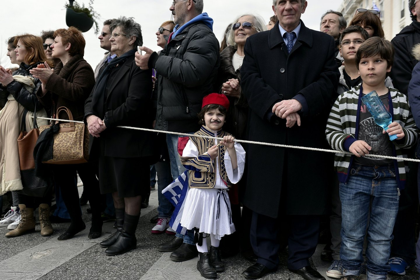 A boy dressed in Greek traditional costume holds a Greek flag, as he watches the student parade on the eve of Greece's Independence day, commemorating the 1821 start of the war against the Ottoman rule on March 24, 2015.  AFP PHOTO/ LOUISA GOULIAMAKI        (Photo credit should read LOUISA GOULIAMAKI/AFP/Getty Images)