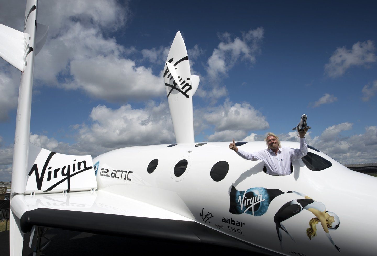 British billionaire Richard Branson poses for photographs in the window of a replica of the Virgin Galactic, the world?s first commercial spaceline, at the Farnborough International Airshow in Hampshire, southern England, on July 11, 2012. Virgin Galactic announced ?LauncherOne,? a new air-launched rocket specifically designed to deliver small satellites into orbit. Commercial flights of the new orbital launch vehicle are expected to begin by 2016, Virgin Galactic aims to offer frequent and dedicated launches at the world?s lowest prices. AFP PHOTO / ADRIAN DENNIS        (Photo credit should read ADRIAN DENNIS/AFP/GettyImages)