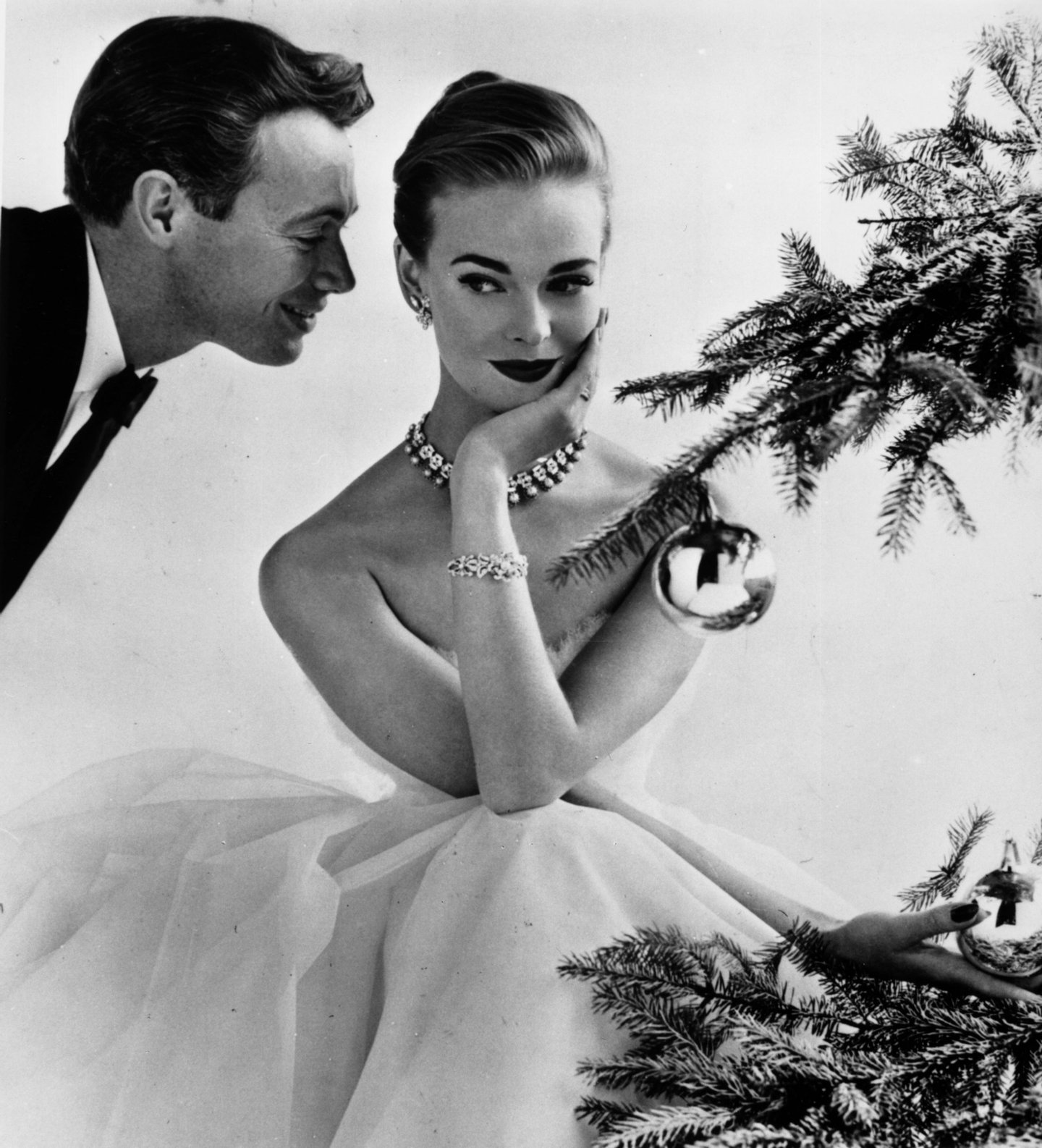 A couple flirting beside a Christmas tree, December 1955. The female model is Susan Abraham. Original Publication: Housewife Magazine - pub. 1955 (Photo by John French/Getty Images)