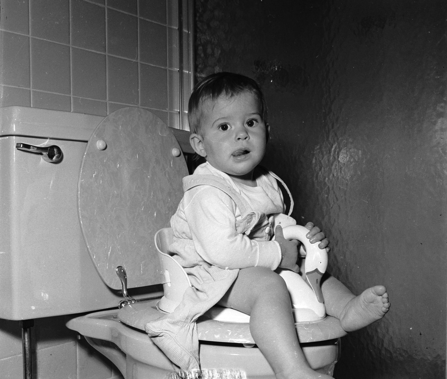 circa 1950:  A one year old learns to use the lavatory with her own special toilet seat.  (Photo by Lloyd Yearwood/Three Lions/Getty Images)
