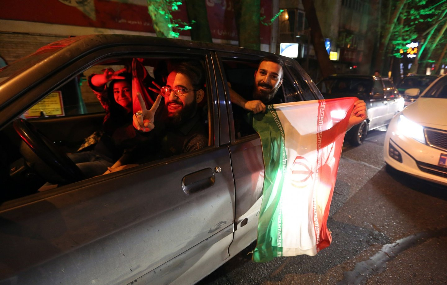 """People flash the """"V for Victory"""" sign and hold an Iranian flag out of a car window as they celebrate on Valiasr street in northern Tehran on April 2, 2015, after the announcement of an agreement on Iran nuclear talks. Iran and global powers sealed a deal on April 2 on plans to curb Tehran's chances for getting a nuclear bomb, laying the ground for a new relationship between the Islamic republic and the West. AFP PHOTO / ATTA KENARE        (Photo credit should read ATTA KENARE/AFP/Getty Images)"""