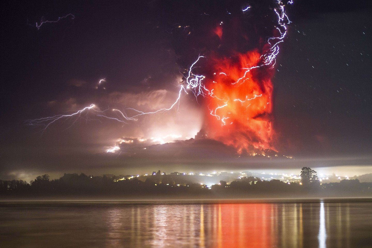 This view from Puerto Varas, southern Chile, shows a high column of ash and lava spewing from the Calbuco volcano, on April 23, 2015. Chile's Calbuco volcano erupted on Wednesday, spewing a giant funnel of ash high into the sky near the southern port city of Puerto Montt and triggering a red alert. Authorities ordered an evacuation for a 10-kilometer (six-mile) radius around the volcano, which is the second in southern Chile to have a substantial eruption since March 3, when the Villarrica volcano emitted a brief but fiery burst of ash and lava. AFP PHOTO/DAVID CORTES SEREY/AGENCIA UNO        (Photo credit should read DAVID CORTES SEREY/AFP/Getty Images)