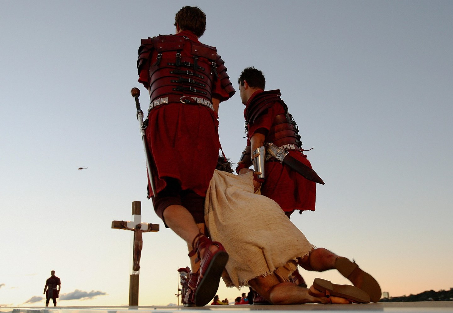 "Jesus (below) is dragged to the cross during a re-enactment at World Youth Day at Barangaroo in Sydney on July 18, 2008. The ""stations of the cross"" re-enactment of the last days of Jesus Christ's life, was being held at some of Sydney's most famous sites and had been expected to draw between 350,000 and 450,000 spectators, organisers said.   AFP PHOTO / Greg WOOD (Photo credit should read GREG WOOD/AFP/Getty Images)"