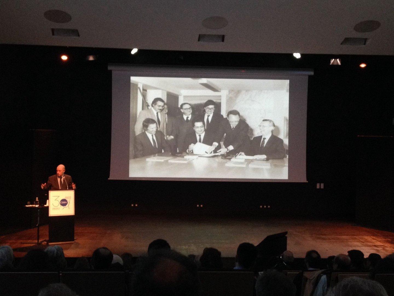 Eduardo Arantes e Oliveira, ex-secretário de Estado da Investigação Científica, durante o discurso de homenagem a Mariano Gago. Ao fundo a fotografia da assinatura do acordo de adesão ao CERN com Jaime Gama, na altura ministro dos Negócios Estrangeiros - D.R.