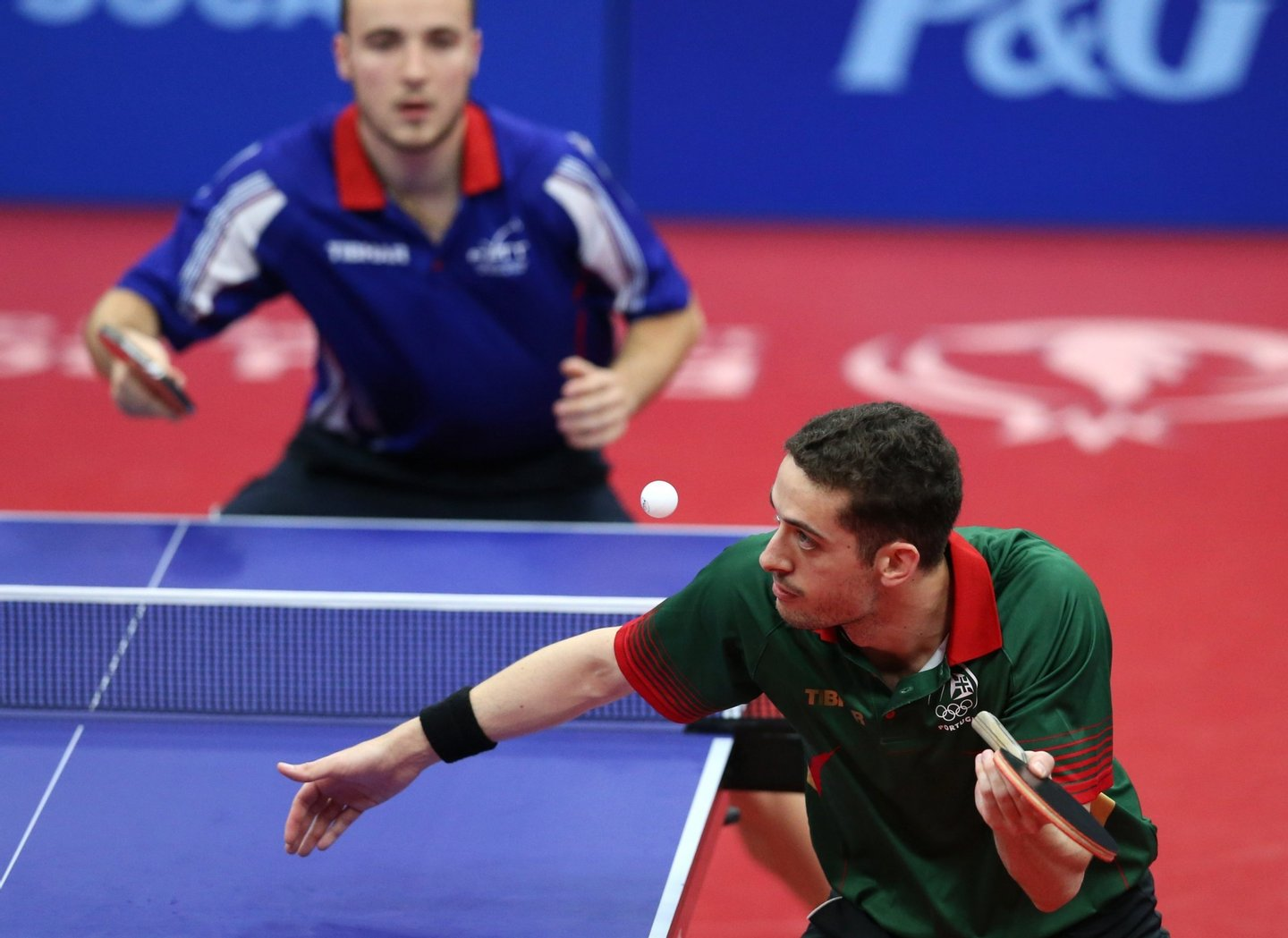 epa04801108 Marcos Freitas (R) of Portugal serves the ball to Simon Gauzy of France during the gold medal match of the men's Table Tennis team event at the Baku 2015 European Games in Baku, Azerbaijan, 15 June 2015.  EPA/ZURAB KURTSIKIDZE