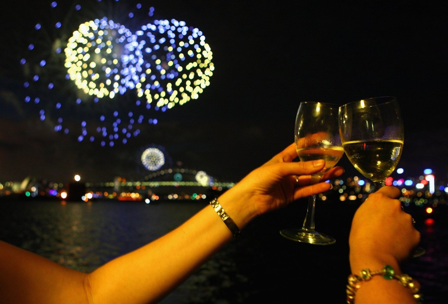 SYDNEY, AUSTRALIA - DECEMBER 31:  People toast their wine glasses as the annual New Year's Eve fireworks display illuminates the sky over Sydney Harbour on December 31, 2009 in Sydney, Australia. The 2009 into 2010 theme is 'Awaken The Spirit' with over 1.5 million people expected to gather around the harbour to watch the 12 minute show.  (Photo by Ryan Pierse/Getty Images)