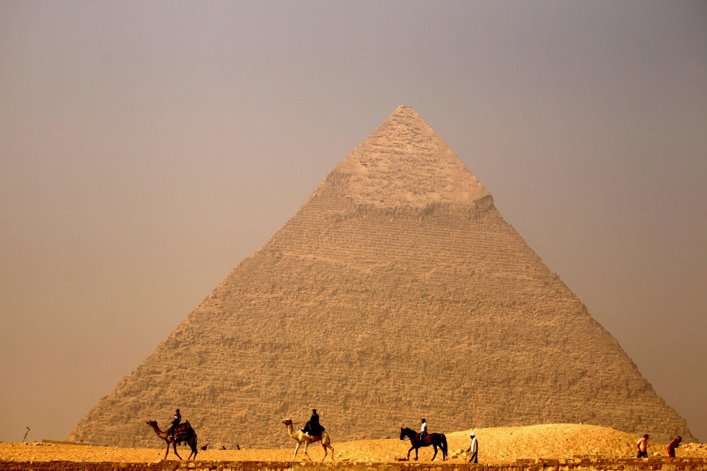 Egyptians ride their camels past the pyramid of Khafre (Chefren) in Giza, on the outskirts of Cairo, on November 30, 2010. AFP PHOTO/PATRICK BAZ (Photo credit should read PATRICK BAZ/AFP/Getty Images)