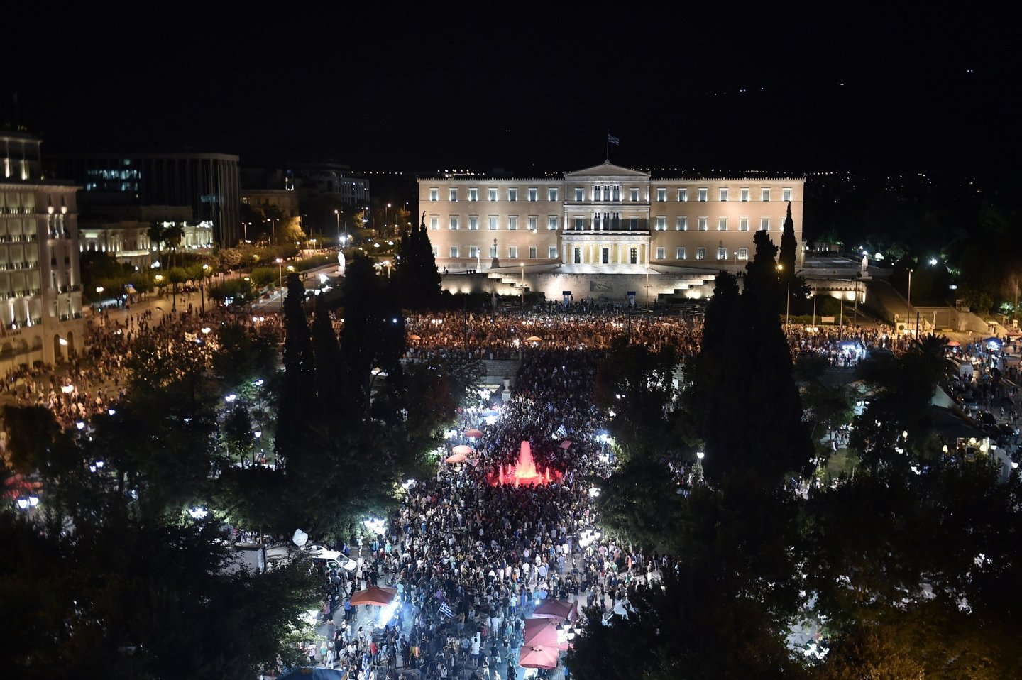 People gather in front of the Greek Parliament in Athens on July 5, 2015, after early results showed those who rejected further austerity measures in a crucial bailout referendum were poised to win. Over 61 percent of Greek voters on July 5 rejected fresh austerity demands by the country's EU-IMF creditors in a historic referendum, official results from 50 percent of polling stations showed.  AFP PHOTO / ARIS MESSINIS        (Photo credit should read ARIS MESSINIS/AFP/Getty Images)