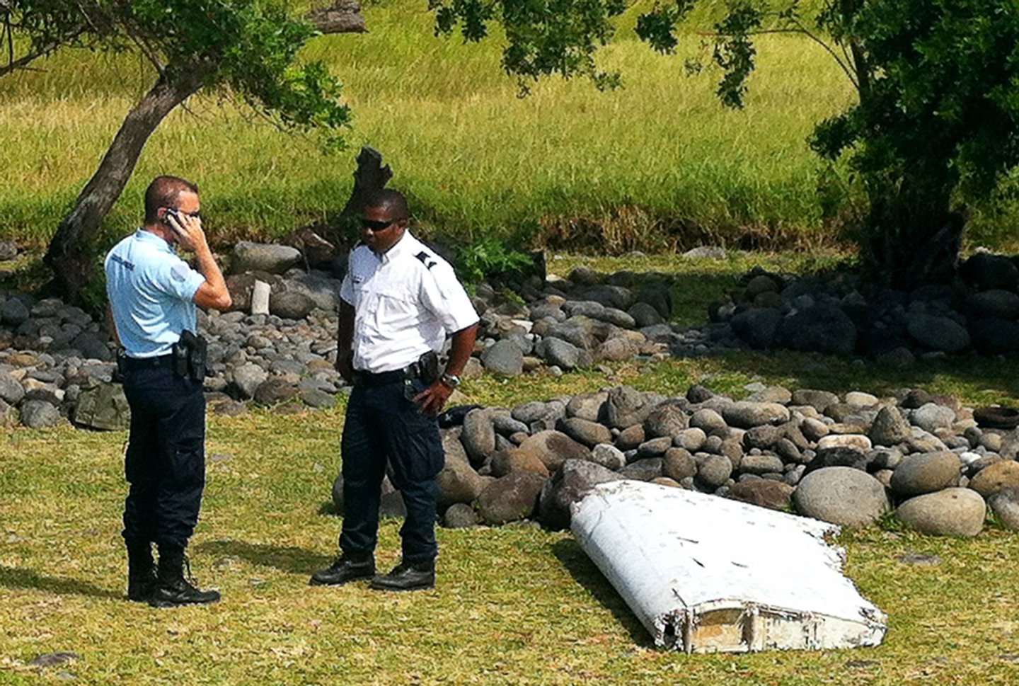 A policeman and a gendarme stand next to a piece of debris from an unidentified aircraft found in the coastal area of Saint-Andre de la Reunion, in the east of the French Indian Ocean island of La Reunion, on July 29, 2015. The two-metre-long debris, which appears to be a piece of a wing, was found by employees of an association cleaning the area and handed over to the air transport brigade of the French gendarmerie (BGTA), who have opened an investigation. An air safety expert did not exclude it could be a part of the Malaysia Airlines flight MH370, which went missing in the Indian Ocean on March 8, 2014. AFP PHOTO / YANNICK PITOU (Photo credit should read YANNICK PITOU/AFP/Getty Images)