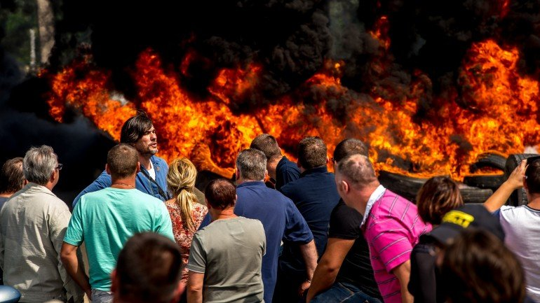 Striking employees of the My Ferry Link company block the access to the harbour after setting tyres on fire on July 31, 2015 in Calais, northern France, following the failure of negotiations with French government concerning job cuts.  AFP PHOTO PHILIPPE HUGUEN        (Photo credit should read PHILIPPE HUGUEN/AFP/Getty Images)