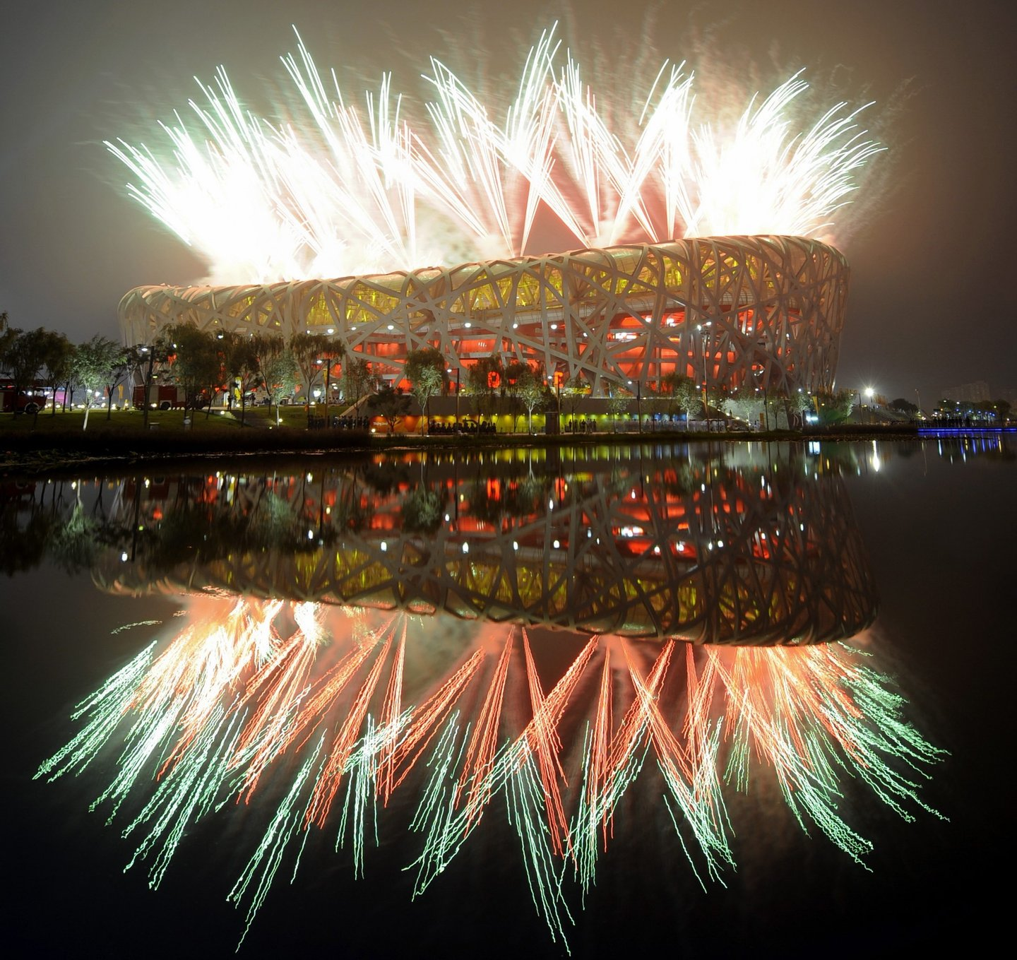 """Fireworks explode next to the National Stadium, also known as the """"Bird's Nest"""",  during the opening ceremony of the 2008 Beijing Olympic Games on August 8, 2008.  A thundering display of fireworks exploded over the """"Bird's Nest"""" stadium in the shape of a blossoming red flower as China put the full glory of its rich history on display at the Olympic opening ceremony. Some 91,000 people, many waving Chinese flags, packed into the National Stadium on a hot and humid night for a spectacular show masterminded by Oscar-nominated filmmaker Zhang Yimou.       AFP PHOTO / FRANCK FIFE (Photo credit should read FRANCK FIFE/AFP/Getty Images)"""