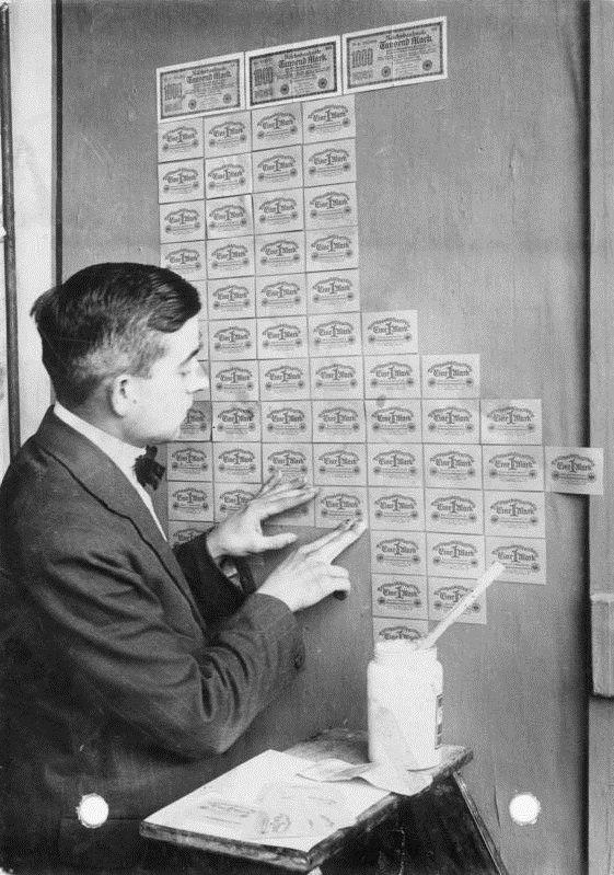Tapezieren einer Wand mit Ein-Markscheinen welche heute um vieles billiger sind wie eine Tapete