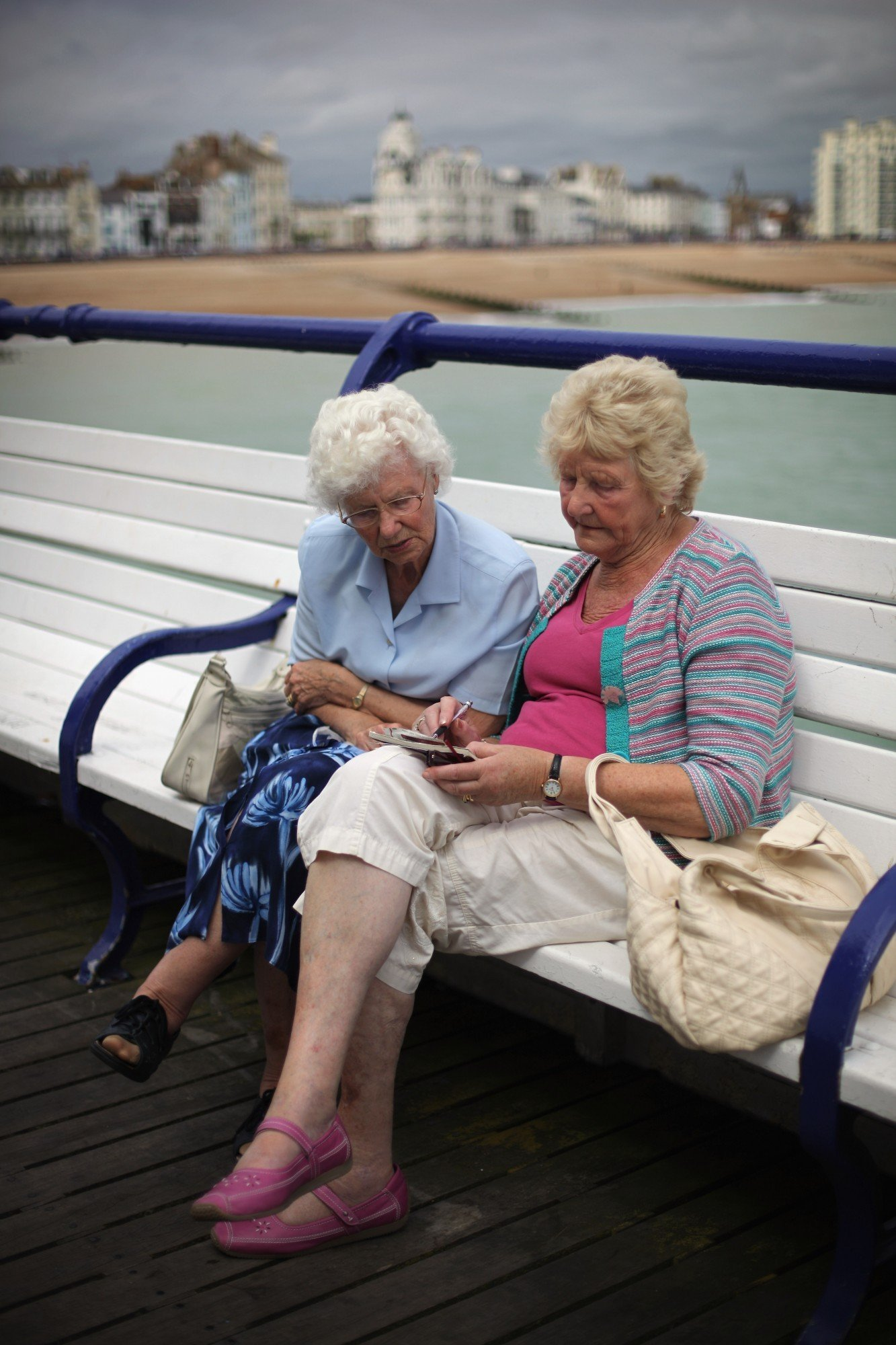 EASTBOURNE, ENGLAND - AUGUST 21: Two women complete a crossword on the pier at Eastbourne on August 21, 2010 in Eastbourne, England. Beach and seaside breaks in the UK have become increasingly popular due to people's nostalgic memories of growing up, according to the British tourist authority, VisitBritain. (Photo by Dan Kitwood/Getty Images)