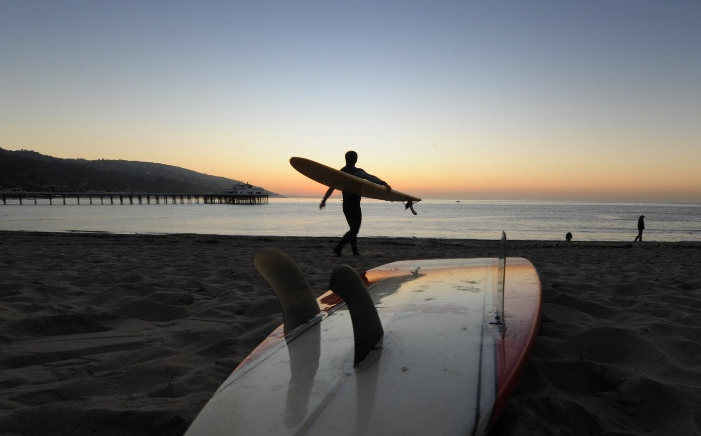 """A surfer enters the water before tribal elder Mati Waiya from the Chumash Nation conducts the dedication ceremony for the iconic Malibu Surfrider Beach to become the first """"World Surfing Reserve"""" (WSR), in Malibu on October 9, 2010. Malibu is California?s definitive pointbreak and one of the world?s first ?perfect waves?, but has struggled with water quality issues in recent years. The WSR program, inspired by UNESCO?s World Heritage Sites, helps the surfing community to identify and preserve it's surfing heritage, raise environmental awareness and issues at important surf breaks.              AFP PHOTO/Mark RALSTON (Photo credit should read MARK RALSTON/AFP/Getty Images)"""