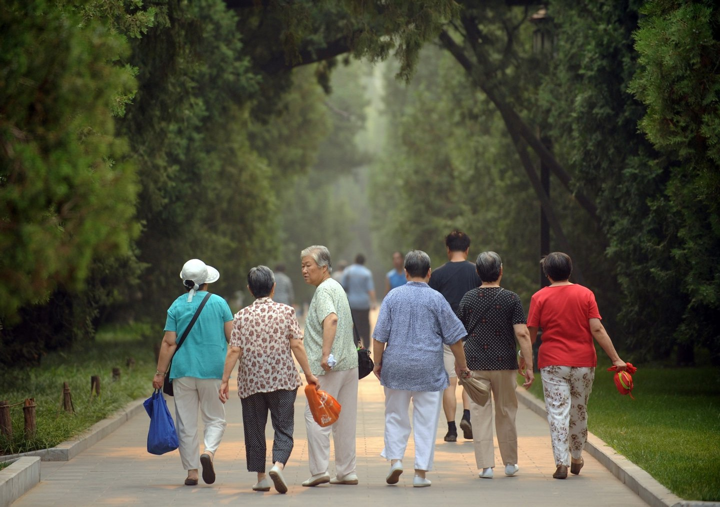 This photo taken on June 28, 2011 shows elderly women heading for their early morning exercises in Ditan Park in Beijing. China's population is ageing and flocking to cities, according to the latest national census results released recently, showing the world's most populous country now counted at 1.339 billion people. AFP PHOTO / Peter PARKS (Photo credit should read PETER PARKS/AFP/Getty Images)