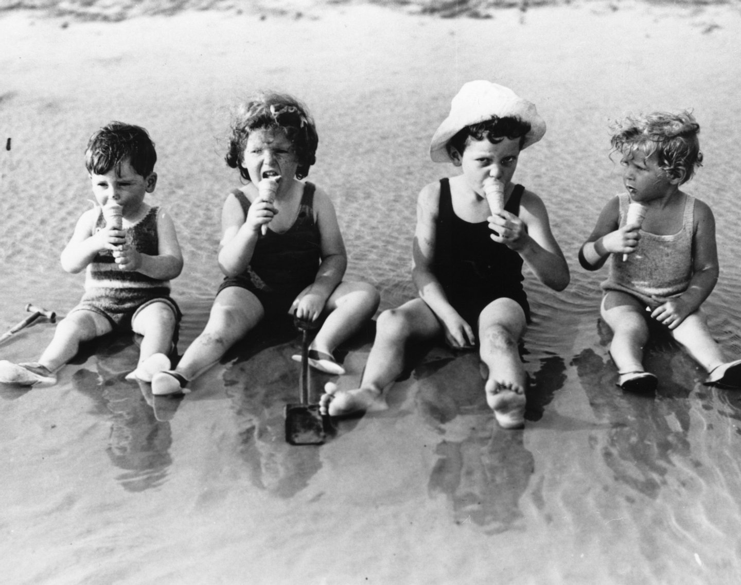 20th July 1935: A group of young children sit in the shallows as they enjoy an ice-cream at Littlehampton. (Photo by Reg Speller/Fox Photos/Getty Images)