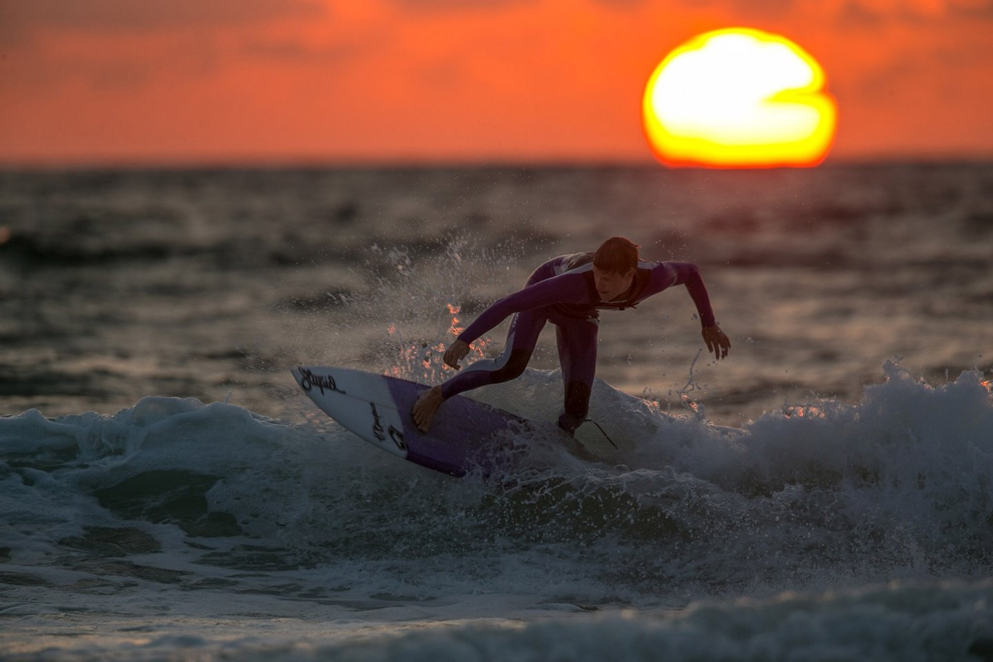 NEWQUAY, UNITED KINGDOM - AUGUST 06:  A surfer catches a wave as the sun sets on Fistral Beach on the first day of the Boardmasters surf and music festival in Newquay on August 6, 2014 in Cornwall, England. Since 1981, Newquay has been playing host to the Boardmasters surfing competition - which is part of a larger five-day surf, skate and music festival and has become a integral part of the continually popular British surf scene growing from humble beginnings, to one of the biggest events on the British surfing calendar. It now attracts professional surfers from across the globe to compete on the Cornish beach that is seen by many as the birthplace of modern British surfing.  (Photo by Matt Cardy/Getty Images)