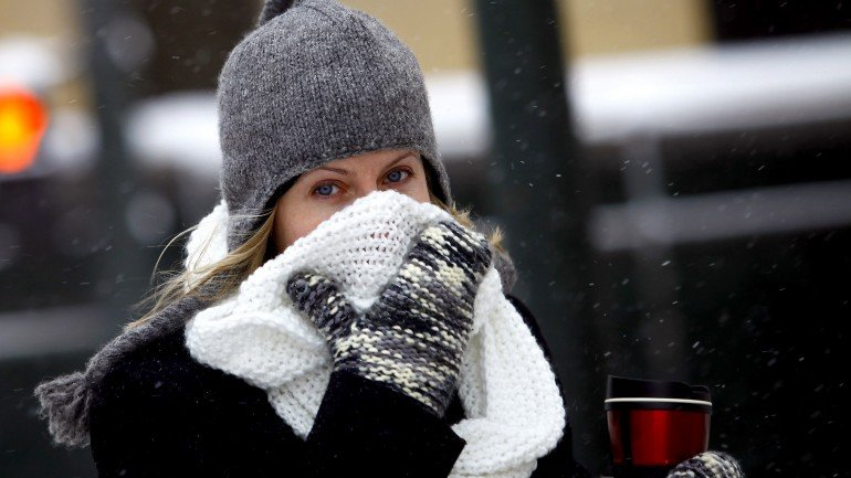 """DETROIT, MI - JANUARY 6: A woman covers her face from the cold as the area deals with record breaking freezing weather January 6, 2014 in Detroit, Michigan. Michigan and most of the Midwest received their first major snow storm of 2014 last week and subzero temperatures are expected most of this week with wind-chill driving temperatures down to 50-70 degrees below zero. A """"polar vortex"""" weather pattern is bringing some of the coldest weather the U.S. has had in almost 20 years. (Photo by Joshua Lott/Getty Images)"""