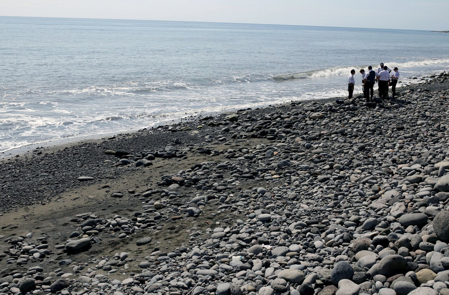 Police officers inspect metallic debris found on a beach in Saint-Denis on the French Reunion Island in the Indian Ocean on August 2, 2015, close to where a Boeing 777 wing part believed to belong to missing flight MH370 washed up last week. A piece of metal was found on La Reunion island, where a Boeing 777 wing part believed to belong to missing flight MH370 washed up last week, said a source close to the investigation. Investigators on the Indian Ocean island took the debris into evidence as part of their probe into the fate of Malaysia Airlines flight MH370, however nothing indicated the piece of metal came from an airplane, the source said. AFP PHOTO / RICHARD BOUHET (Photo credit should read RICHARD BOUHET/AFP/Getty Images)