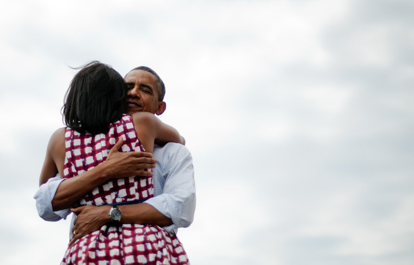 First Lady Michelle Obama (L) and US President Barack Obama (R) hug after delivering remarks during a campaign event at the Alliant Energy Amphitheater in Dubuque, Iowa, August 15, 2012, during his three-day campaign bus tour across the state. AFP PHOTO/Jim WATSON (Photo credit should read JIM WATSON/AFP/Getty Images)