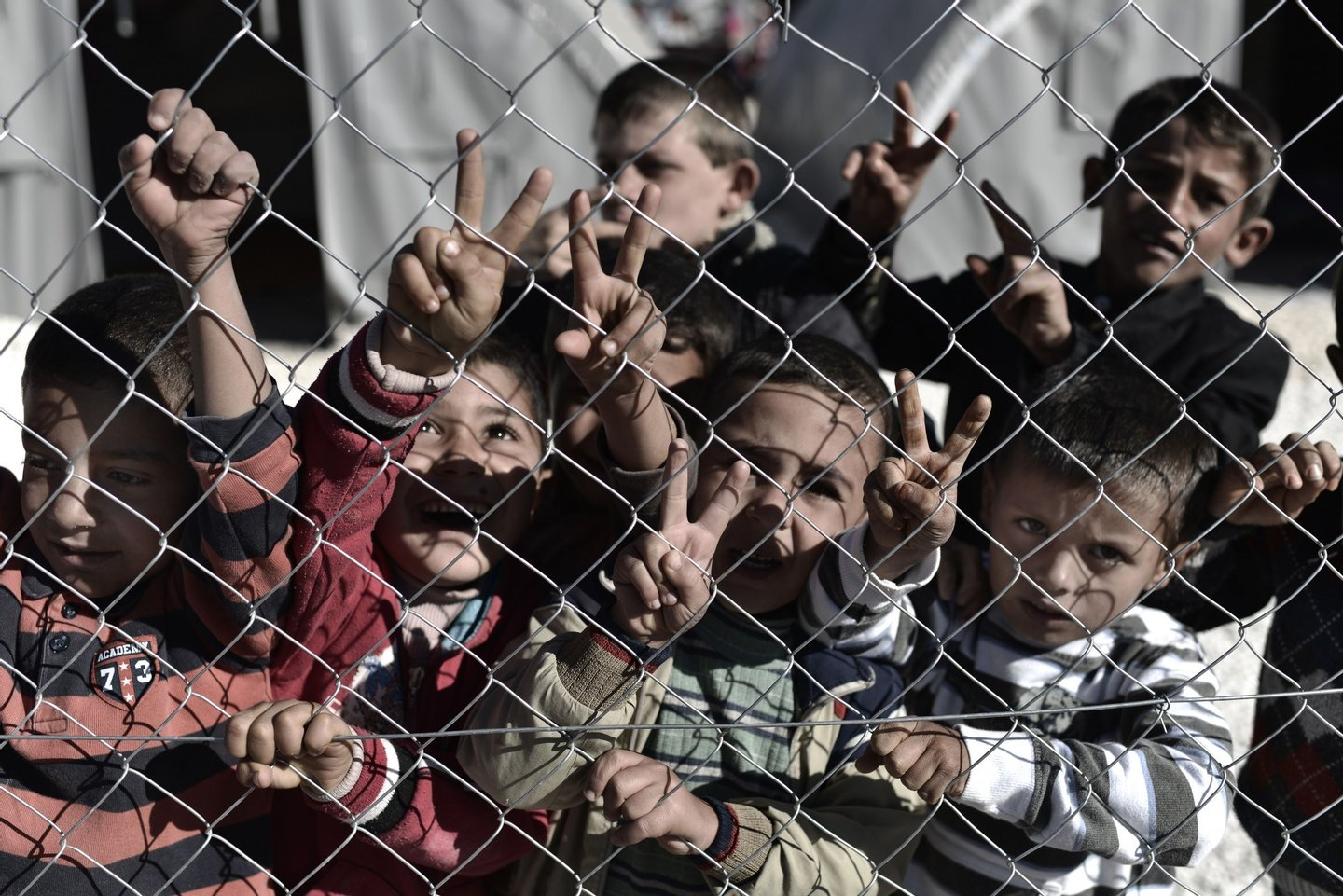 "Young Syrian Kurdish boys make the ""V for victory"" sign behind a fence at a refugee camp in the town of Suruc, Sanliurfa province, on November 5, 2014. Iraqi Kurdish peshmerga fighters who joined the battle for the Syrian border town of Kobane have been heavily shelling Islamic State group jihadists, a commander told AFP. AFP PHOTO / ARIS MESSINIS (Photo credit should read ARIS MESSINIS/AFP/Getty Images)"